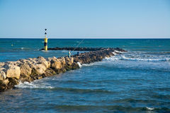 Men fishing from the pier. PALMA DE MALLORCA, BALEARIC ISLANDS, SPAIN - JUNE 29, 2017: Men fishing from the pier at Molinar beach on a summer evening on June 29 Royalty Free Stock Images
