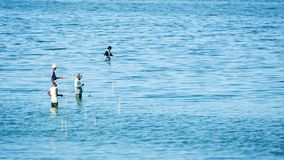 Men with fishing rod stand in water of Taungthaman lake Stock Photo