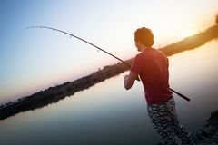 Men fishing in sunset and relaxing while enjoying hobby Stock Photos