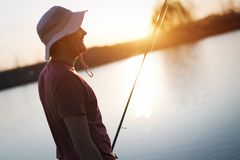 Men fishing in sunset and relaxing while enjoying hobby. Men fishing in sunset and relaxing and enjoying hobby Royalty Free Stock Photography