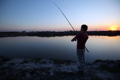 Men fishing in sunset and relaxing while enjoying hobby. Men fishing in sunset and relaxing and enjoying hobby Royalty Free Stock Photo