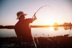Men fishing in sunset and relaxing while enjoying hobby. Men fishing in sunset and relaxing and enjoying hobby Stock Photo
