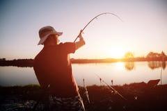 Men fishing in sunset and relaxing while enjoying hobby Stock Photo