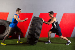 Men flipping a tractor tire workout gym exercise. Men flipping a tractor tire workout exercise at gym royalty free stock image