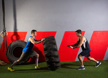 Men flipping a tractor tire workout gym exercise. Men flipping a tractor tire workout exercise at gym royalty free stock images