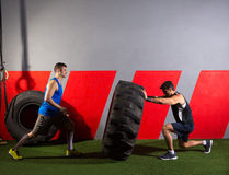 Men flipping a tractor tire workout gym exercise. Men flipping a tractor tire workout exercise at gym stock photos