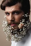Men With Flowers In Their Beards. Creative Portrait of young beautiful man with a beard decorated with flowers stock photo