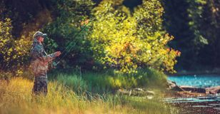 Men Fly Fishing in a River. Caucasian Men in His 30s Fly Fishing in a River in Sunny Summer Day stock images