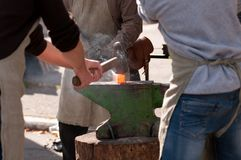 Men forge on the anvil Royalty Free Stock Image