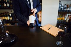 Men in formal clothes holding a red wine bottle in wine store. Men in formal clothes holding a red wine bottle with white blank label in wine store or restaurant royalty free stock image