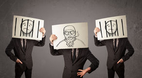 Men in formal gesturing with cardboard in front of their head Royalty Free Stock Images