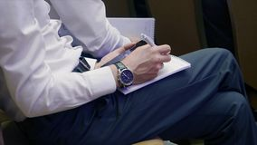 Men on the forum writes important information in exercise book, take notes. Stock. Close up of hand.  stock photography
