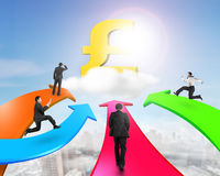 Men on four color arrows go toward golden pound symbol. On cloud in sky stock photography