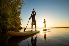 Men, friends sail on a SUP boards in a rays of rising sun. Stand up paddle boarding - awesome active recreation in nature. Backlight, wide angle stock photo