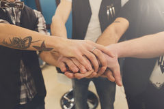 Men friendship. United hands of young team with tattoo. Unity and teamwork concept Royalty Free Stock Photography