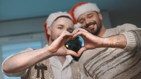 Men gay couple with santa hats making heart shape with their hands