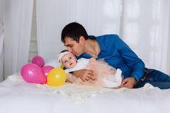 A man gently kisses his little baby lying on the bed. A girl in white pantyhose and a pink skirt calmly lies with her. A men gently kisses his little baby lying royalty free stock images