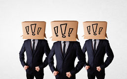 Men gesturing with exclamation marks on box on their head Royalty Free Stock Image