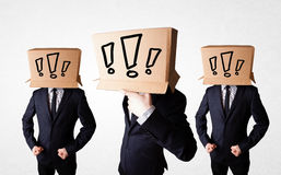 Men gesturing with exclamation marks on box on their head Royalty Free Stock Photography