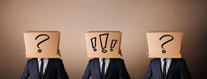 Men gesturing with exclamation marks on box on their head Stock Photos