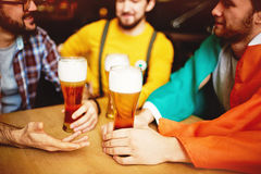 Men Get Together in Craft Beer Pub. Three men meeting in Irish Pub enjoying conversation and craft beer, focus on tall glasses on table royalty free stock image