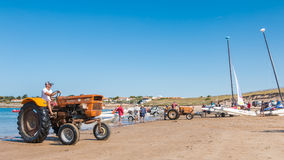 Men getting boats out of water with tractors on the beach Royalty Free Stock Photo