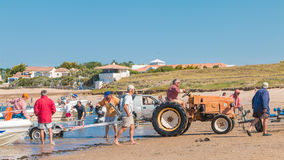 Men getting boats out of water with tractors on the beach Royalty Free Stock Photos