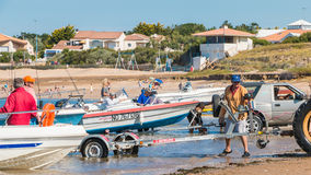 Men getting boats out of water with tractors on the beach Royalty Free Stock Photography