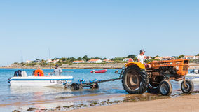 Men getting boats out of water with tractors on the beach Royalty Free Stock Image