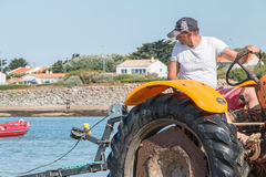Men getting boats out of water with tractors on the beach Stock Photos