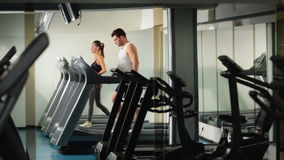 A men and a girl running on the treadmill at the gym stock video
