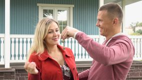 The man gives the woman the keys to the house.Happy couple holding house key on a Sunny day. Surprise. royalty free stock photography
