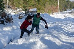 Teamwork couple is helping each other on snow in winter stock photography