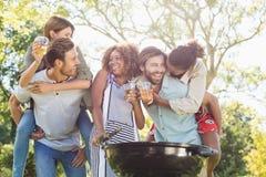 Men giving piggyback to women while preparing barbecue in park Stock Photos