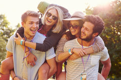 Men Giving Woman Piggybacks On Their Way To Music Festival Royalty Free Stock Photography
