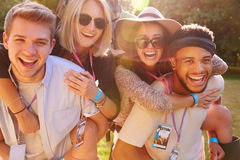 Men Giving Woman Piggybacks On Their Way To Music Festival stock photo