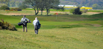 Men on golf course walking towards Pin with golf bags. stock image
