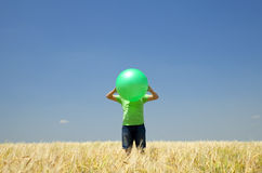 Men with green ball at wheat field. Royalty Free Stock Images