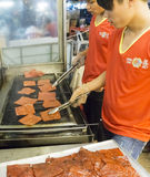 Men grilling dried meat. KUALA LUMPUR, MALAYSIA - AUGUST 29: Shop workers grilling dried pork meat in Jalan Alor Chinatown, Kuala Lumpur on August 29, 2014. Very royalty free stock photo