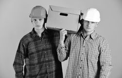 Men with grumpy faces hold cardboard box on pink background. Delivery, warehouse and packaging concept. Siblings with royalty free stock images