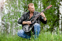 Men with guitar. Young man playing guitar in a grass field stock images