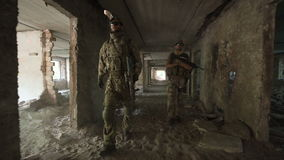 Men with guns walking among ruins. Two men in special clothing holding guns and walking slowly inside of ruined building stock footage