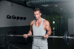 Men In The Gym Exercising Biceps With Barbell Stock Photography