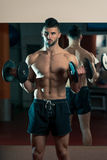 Men In Gym Exercising With Dumbbells Royalty Free Stock Image