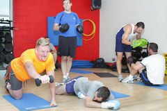 Men gym training workout. Young men workout in the gym, one man has collapsed with exhaustion. People seeing the importance of a healthier lifestyle and training royalty free stock photo