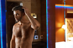 Men Hair Care. Handsome Man Touching His Hair. Men Grooming. Men Hair Care. Portrait Of Handsome Man With Naked Body Touching His Thick Hair Looking At Mirror stock photos