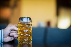 Men Hand with glass mug of golden Freshly filled beer. Real scene in bar, pub. Beer culture, Craft brewery, uniqueness royalty free stock photography