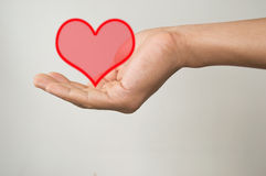 Men hand holding heart  on gray Royalty Free Stock Images