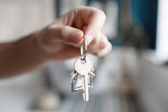 Men hand holding key with house shaped keychain. Modern light lobby interior. Mortgage concept. Real estate, moving home. House key and keychain in the form of stock photography