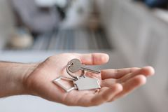 Men hand holding key with house shaped keychain. Modern light lobby interior. Mortgage concept. Real estate, moving home. House key and keychain in the form of royalty free stock photos
